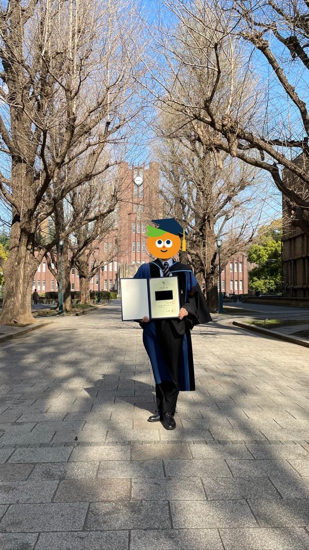 博士卒業時にガウンを着て学位記と一緒に写真